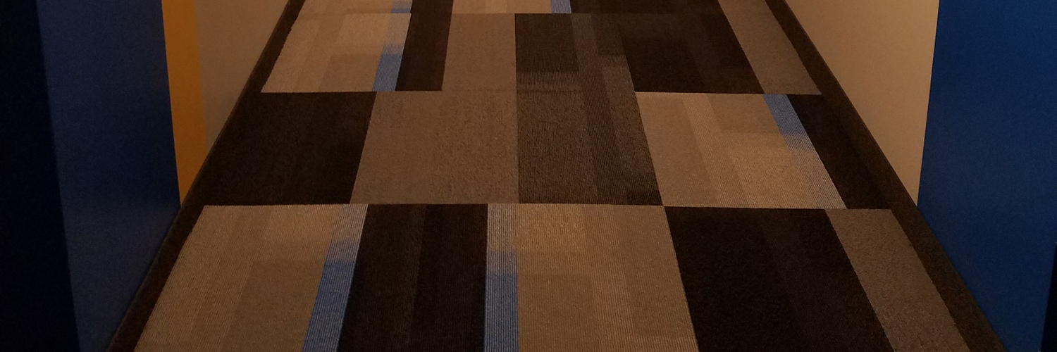 Non-patterned Carpet Tile in an apartment building hallway