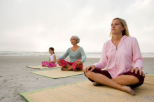 Two women and a girl on a beach meditating