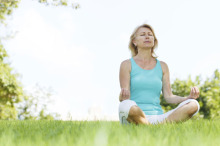 Woman sitting in the grass meditating