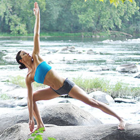 Woman In Yoga Posture On Rocks