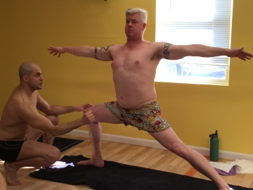 Yoga Instructor Assisting Student in Class at Bikram Yoga Roslyn