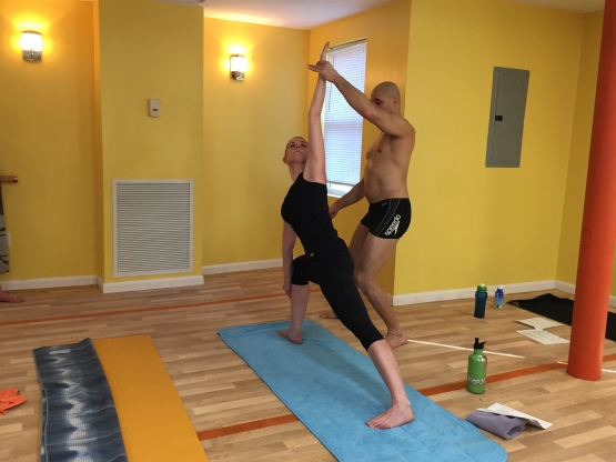 Yoga Instructor Assisting Female Student in Class at Bikram Yoga Roslyn