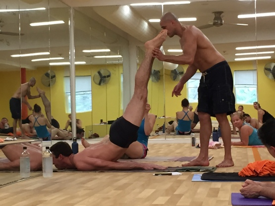 Bikram Yoga Instructor Assisting Male Student in Class at Bikram Yoga Roslyn
