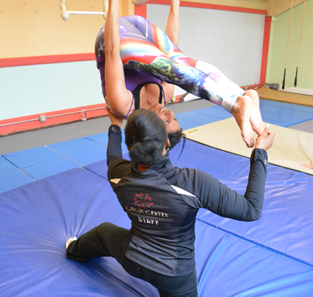 Teacher guides student as to how to properly execute a static trapeze exercise | Circus Center | San Francisco