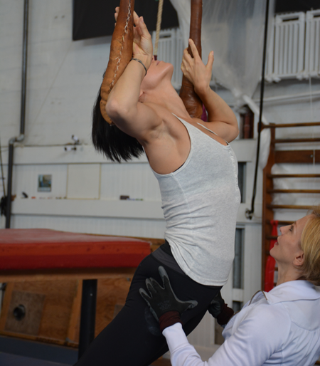 Teacher Elena Panova guides student through a single point trapeze exercise | Circus Center | San Francisco