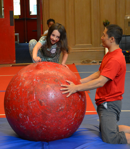 Students joyfully struggles to climb on to the rolla bolla with the teachers' assistance | Circus Center | San Francisco