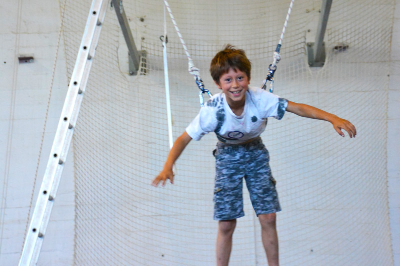 Child smiling while on the flying trapeze | Kids Parties | Circus Center