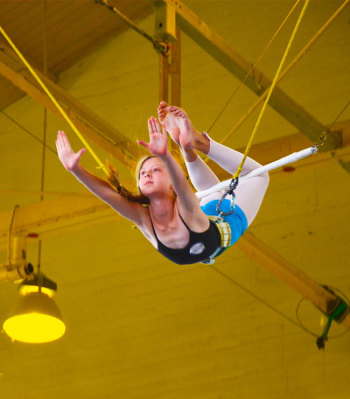 Youn person swinging on the flying trapeze | Kids Parties | Circus Center