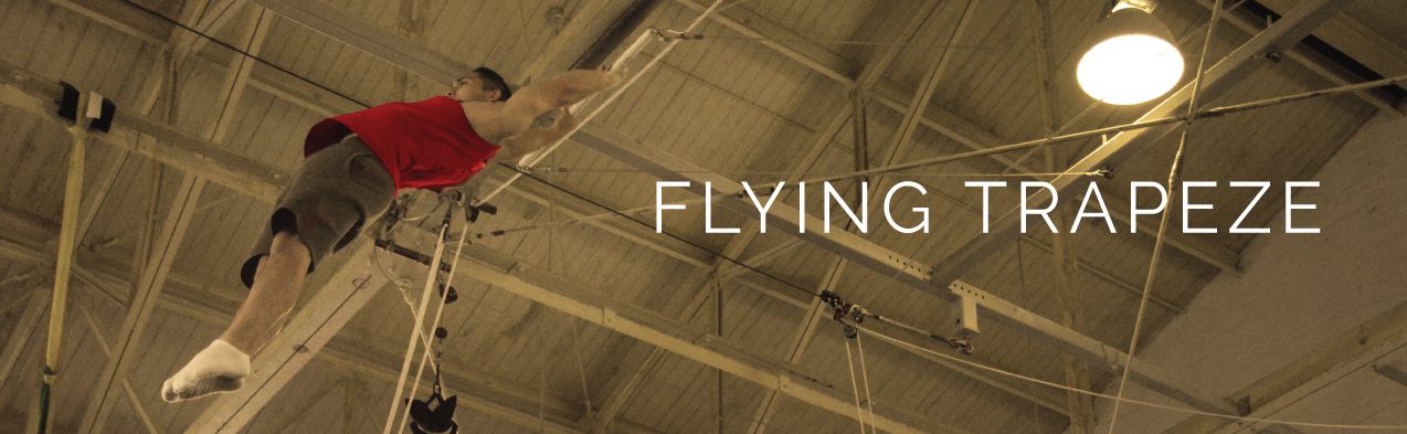 Performer swinging on the flying trapeze | Circus Center